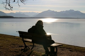 Man sitting on a bench looking at the water
