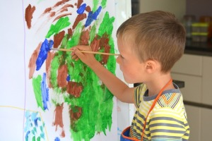 Young boy painting at an easel