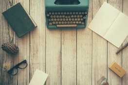 Typewriter, paper, glasses, pen, book on a wooden surface