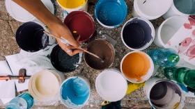 Hand of artist dipping brush into colored cups of paint