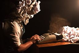 A writer whose head is composed of crumpled paper uses a typewriter.