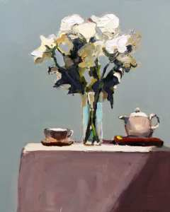 White flowers iin vase on table with teapot and cup