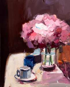 Pink Hydrangeas in vase on white tablecloth with white cup and blue bowl