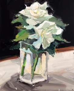 Two white gardenias and leaves in rectangular glass vase