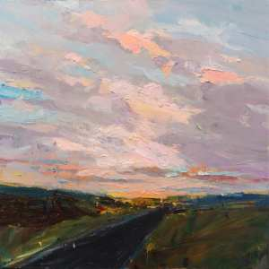 dark grey road receding into cloudy sky with pinks and lavenders