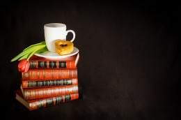 Stack of books with coffee and pastry on top