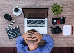 Man in front of laptop, holding his head in frustration