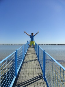 Man on a pier jumping for joy