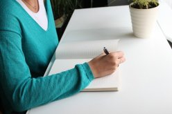 Woman in aqua sweater writing in a book