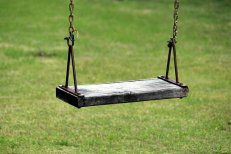 wooden swing on a background of green grass