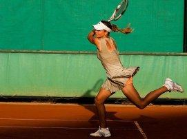 Woman swinging attennis racket on tennis court