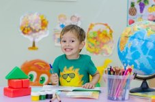 Smiling child with art supplies
