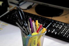 container of pens, pencils, and highlighters in front of a computer keyboard